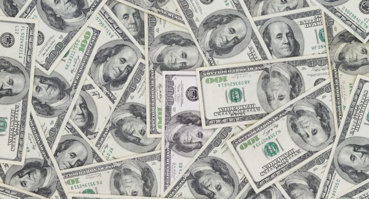 Hundreds of new Benjamin Franklin 100 dollar bills arranged randomly with the portrait facing up