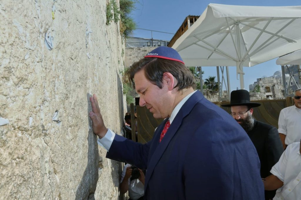 Governor Ron DeSantis, wearing a yarmulke, with his hand on the Western Wall in Jerusalem.
