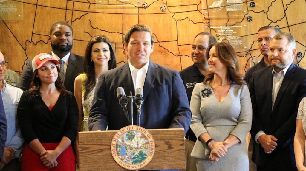 Governor Ron DeSantis standing at a podium speaking at the Audubon Corkscrew Swamp Sanctuary in Naples.