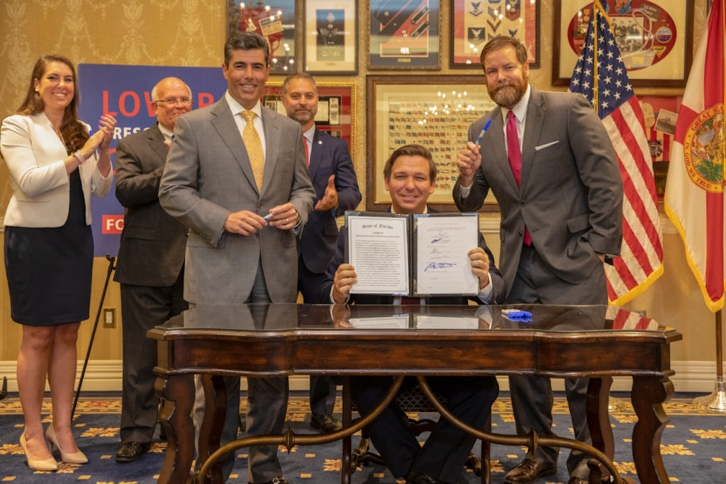 Governor Ron DeSantis pictured holding up bill he signed today.