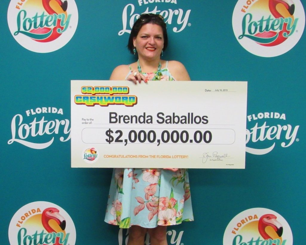 Brenda Saballos poses with her oversized check after claiming a $2 million top prize from the $2,000,000 CASHWORD Scratch-Off game at Florida Lottery Headquarters.
