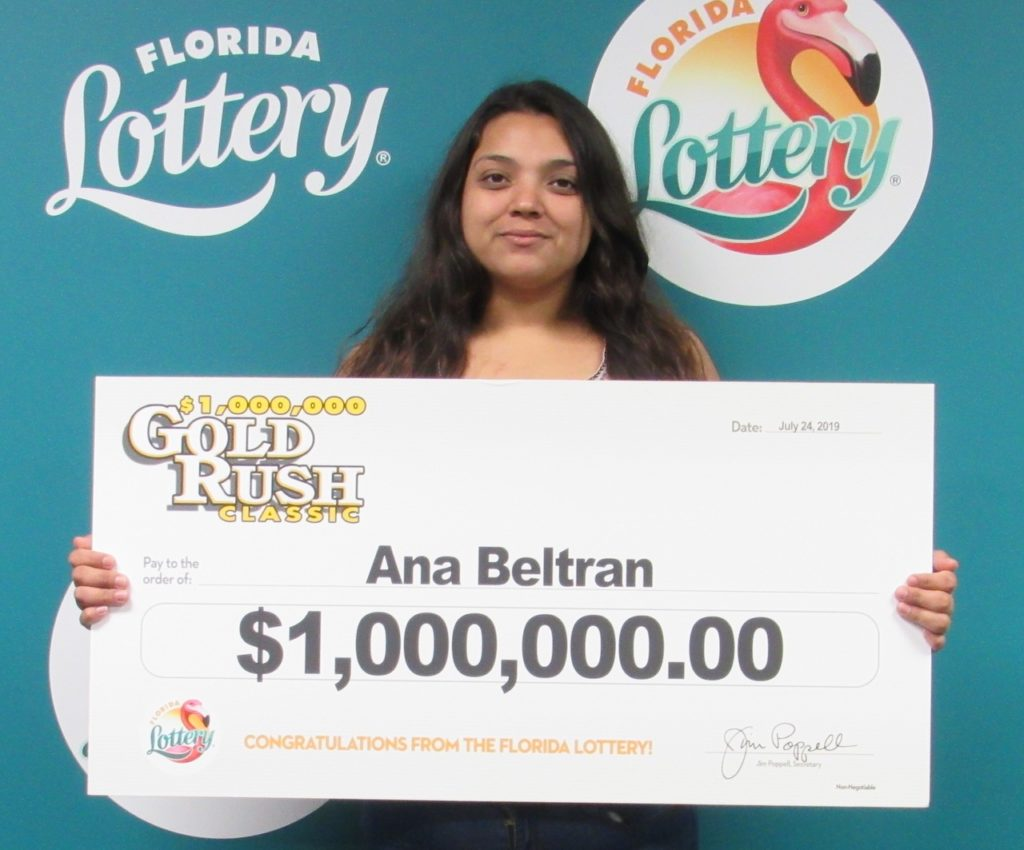 Ana Beltran poses with her oversized check after claiming a $1 million prize from the $5 GOLD RUSH CLASSIC Scratch-Off game at Florida Lottery Headquarters.