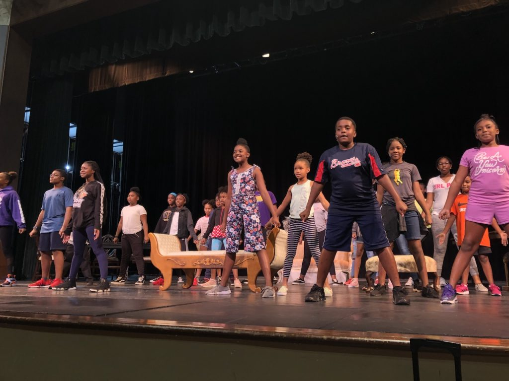 Photograph of the theatre camp children performing on stage.