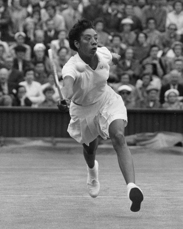 Black and white action photograph of Althea Gibson on the court.