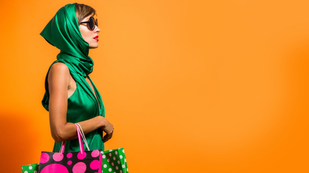 Young happy summer shopping woman with shopping bags isolated over bright orange background
