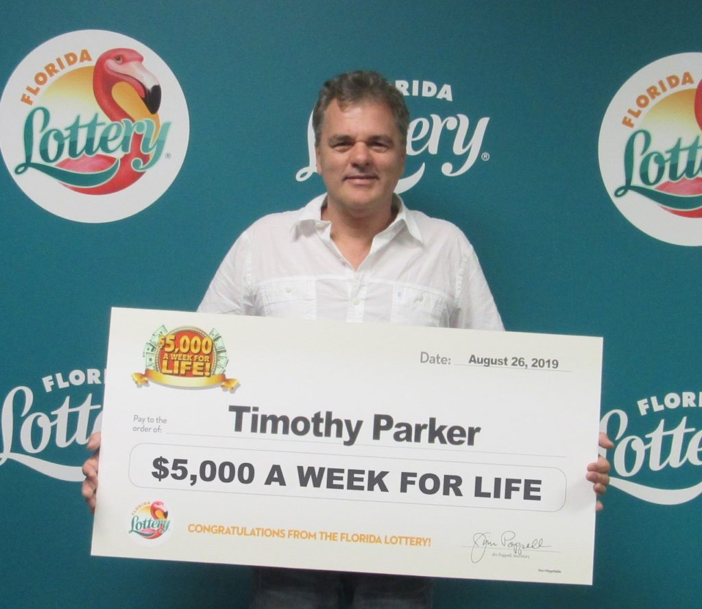 Timothy Parker poses with his oversized check after claiming a top prize in the $5,000 A WEEK FOR LIFE Scratch-Off game at Florida Lottery Headquarters.