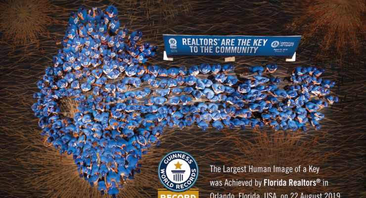 Aerial photograph of 314 Realtors (dressed in blue) standing in the shape of a key.
