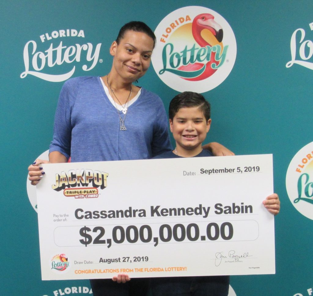 Cassandra Kennedy Sabin poses with her son and oversized check after claiming a $2 million JACKPOT TRIPLE PLAY jackpot from the August 27, 2019 drawing at Florida Lottery Headquarters.