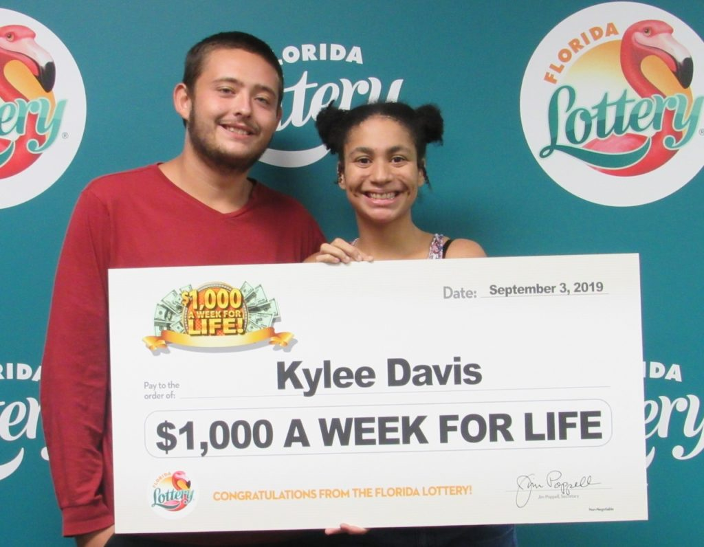 Kylee Davis poses with her boyfriend and oversized check after claiming a top prize in the $1,000 A WEEK FOR LIFE Scratch-Off game at Florida Lottery Headquarters.