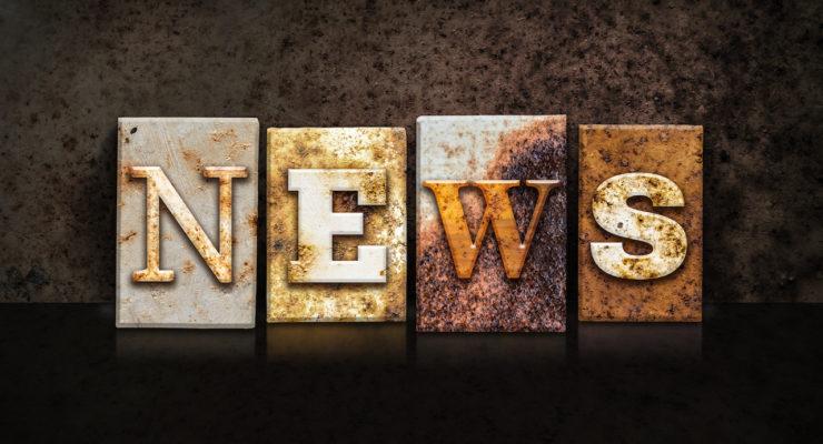 "The word ""NEWS"" written in rusty metal letterpress type on a dark textured grunge background."