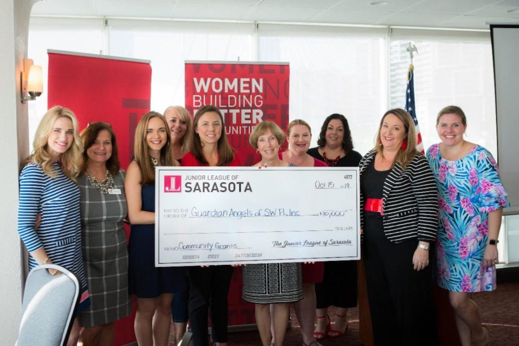 Junior League of Sarasota members hold large check for community grants.