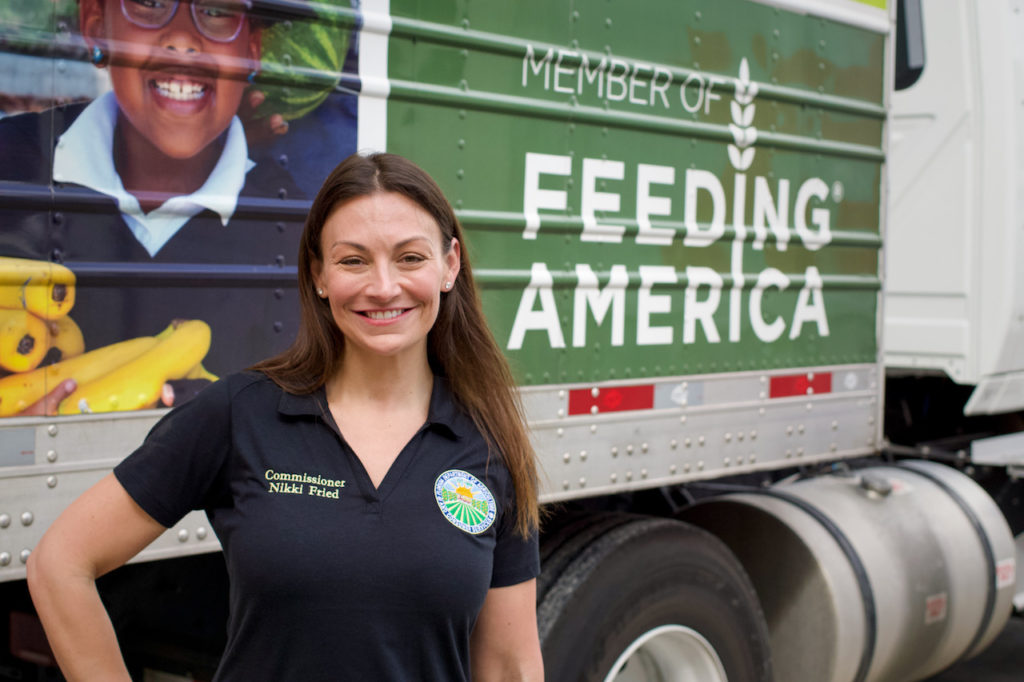 Commissioner Nikki Fried poses in front of a Feeding America truck while touring Pero Farms.