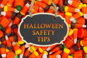 Halloween Safety Tips Message with candy corn on a hanging retro chalkboard