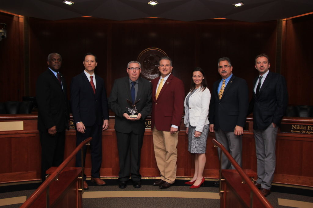 The Florida Cabinet pictured with Insurance Fraud Detective DeWayne White, the 2019 Law Enforcement Officer of the Year.