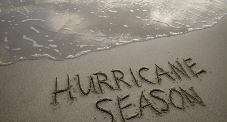 Hurricane Season message handwritten in smooth sand on the shore of a dark and stormy beach